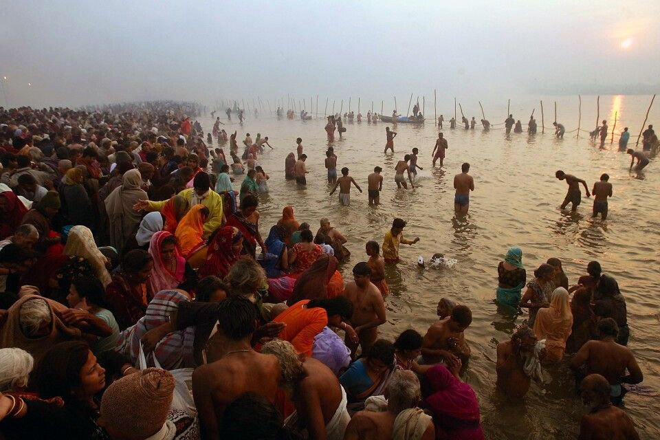 ALLAHABAD, INDIA - JANUARY 23:  Hindu pilgrims gather to bathe at sunrise at the ritual bathing site at Sangam, the confluence of the Ganges, Yamuna and mythical Saraswati rivers during the Ardh Kumbh Mela festival (Half Pitcher festival) January 23, 2007