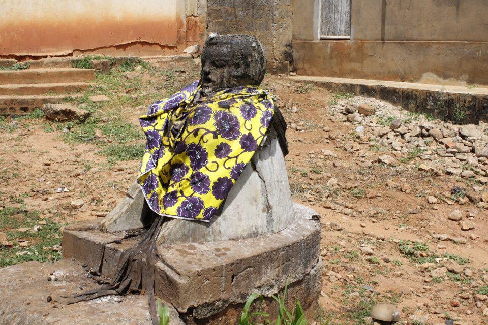 Legba Statue in Togoville. Legba ist der Hüter der Wegkreuzungen und ist vor allem in Nigeria, Benin und Togo in jedem Dorf anzutreffen. Er beschützt das Dorf/die Stadt und seine Bewohner und erhält von diesen Geschenke und Opfergaben zurück.